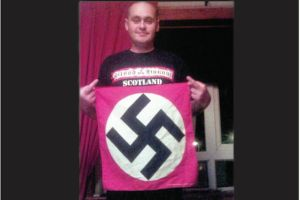 Racist thug James Boyd poses with a Nazi flag